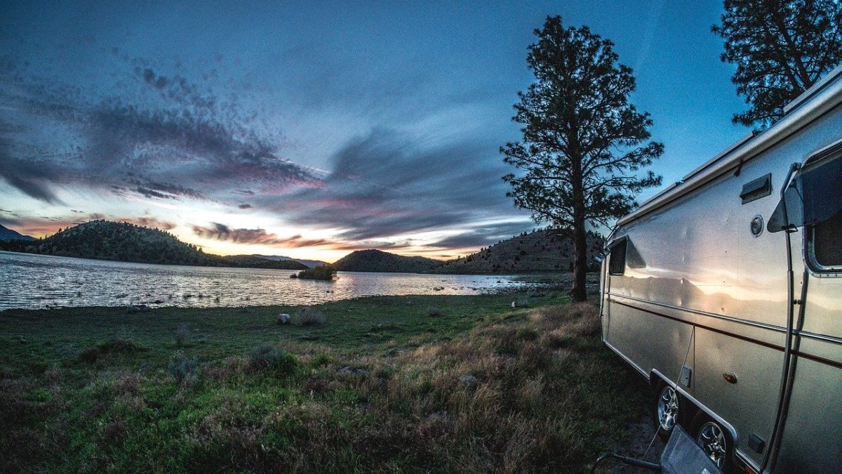 airstream by a river with a beautiful sunset