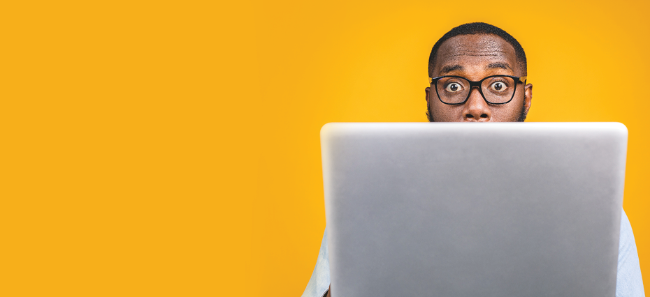 yellow background with man surprised behind the laptop wearing glasses