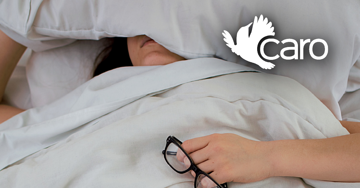 Woman in bed with glasses in hand